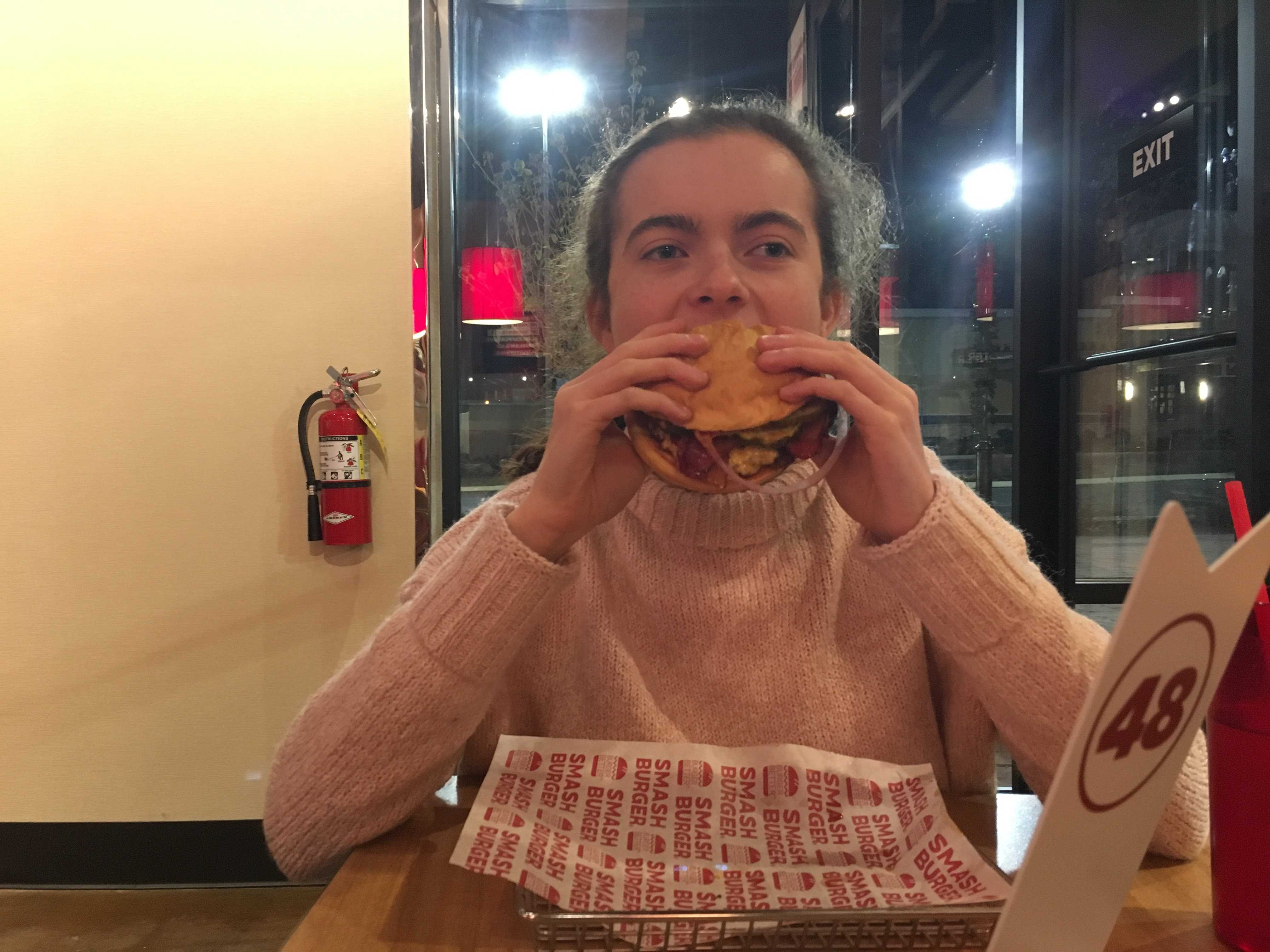 Andrea takes her first bite of her burger.