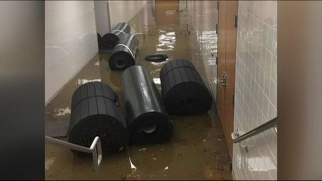 A hallway near the athletic wing flooded with water and sports equipment.