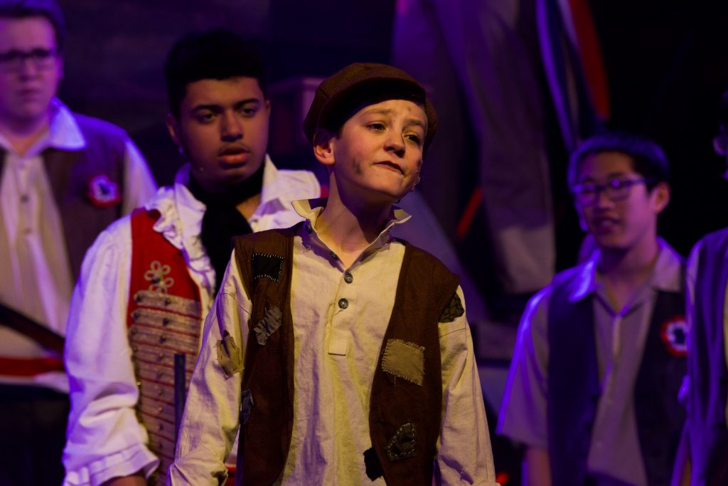 Gavroche+%28Aiden+Panko%29+warns+the+men+that+there+is+a+spy+among+them+in+the+barricade.+Photo+by+Emma+Brashear.