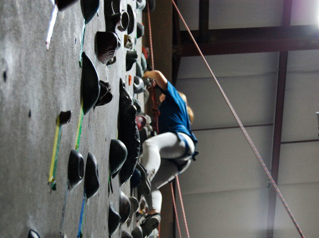 Freshman Maryn Schellenberg, new to rock climbing, climbs on a set of rocks for beginners. Photo by Meliha Anthony.