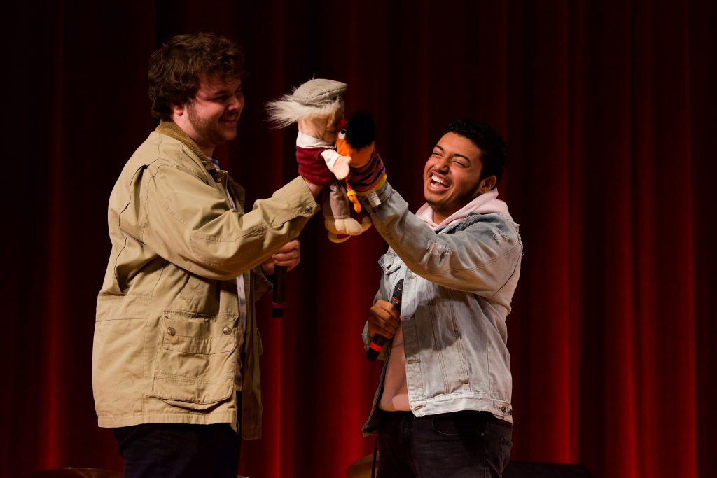 "Seniors Trevor Warren (left) and Lorenzo Antigua (right) finish their cover of ""Man or Muppet"" with a romantic moment between their own muppets. Photo by Emma Brashear."