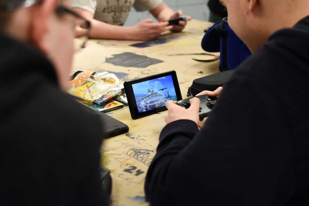 Game+club+members+gather+around+a+Nintendo+Switch+to+play+Super+Smash+Bros.+Ultimate.+Photo+by+Emma+Brashear.+