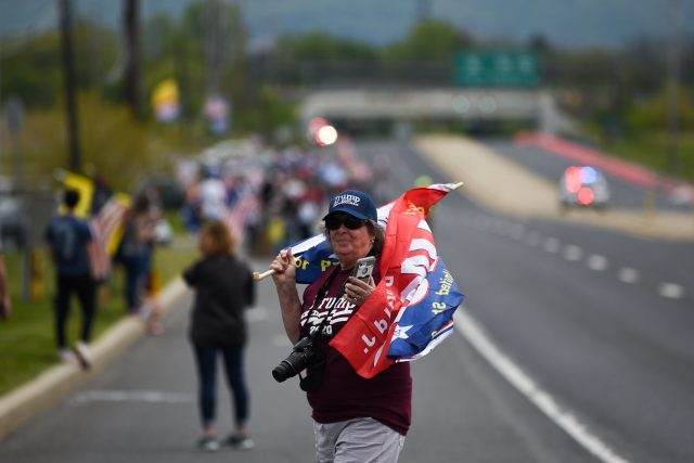 A woman crosses Route 100 to join the crowd of people waiting on the side of the road the president's motorcade would arrive on later that afternoon. Photo by Emma Brashear.