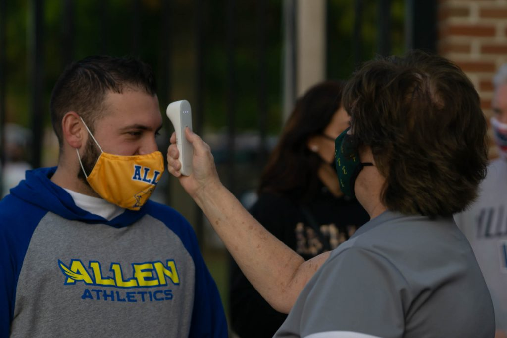 An employee checks the temperature of a patron at the football game on Thursday, which was required of anyone who would be on the field. In addition to this, spectators were asked to wear masks and socially distance. Photo by Alice Adams.