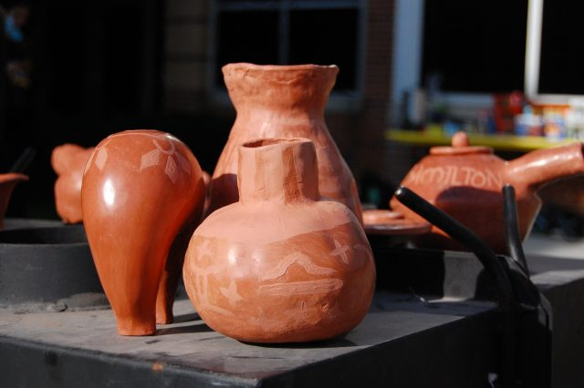 Students' clay pottery pieces sit atop the kiln during the firing. Raku is a specific type of firing where pottery is removed from the hot kiln and left to cool in the open, outside air. Photo by Meliha Anthony.