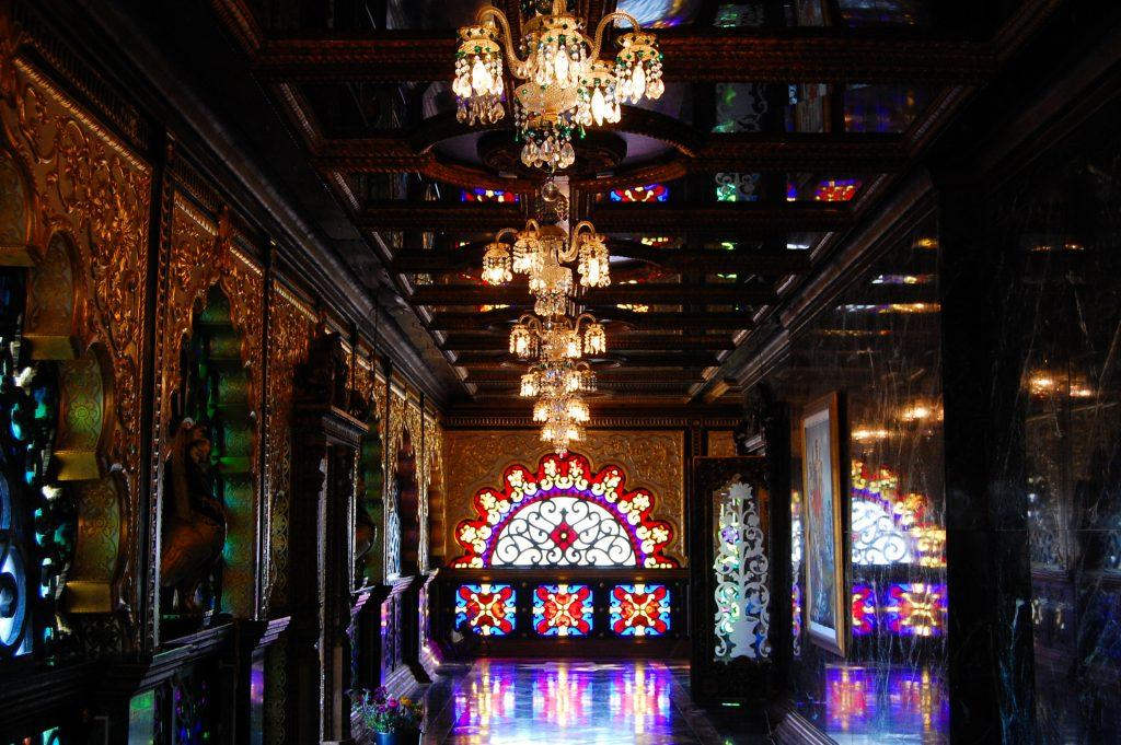The inside of the Palace of Gold is relatively dark, although chandeliers across the ceiling help illuminate it, and sunlight spills in through the elaborate stained glass windows. Photo by Meliha Anthony.