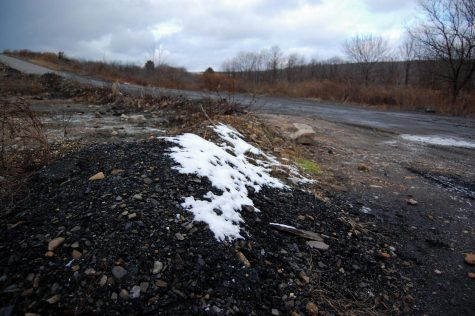 A thin layer of snow covers piles of rocks in the desolate Centralia landscape. Photo by Meliha Anthony.