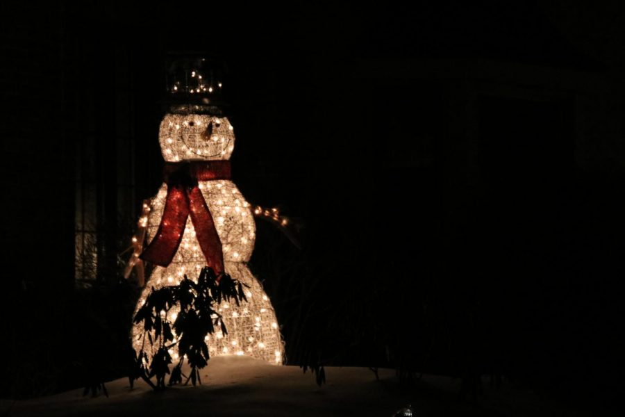 A brightly lit snowman smiles in the snow that accumulated earlier this week. Photo by Bethany Brown.