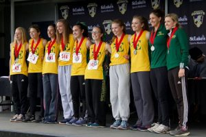 Cross crountry runners pose after winning first place in the 2018 District 11 championship meet with coaches Kelly Bracetty (second from right) and Kami Reinhard.(far right). Bracetty's contract was not renewed. Contributed photo.