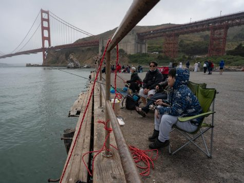 A group of fishermen await a catch at Moore Road Pier, a viewing spot for the Golden Gate Bridge, on June 19, 2021. The pier, a beloved tourist destination, is also a popular spot for fishing. Photo by Alice Adams.