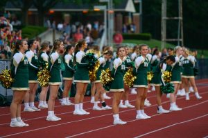 Cheerleaders wait between routines at the football game. Photo by Alice Adams.